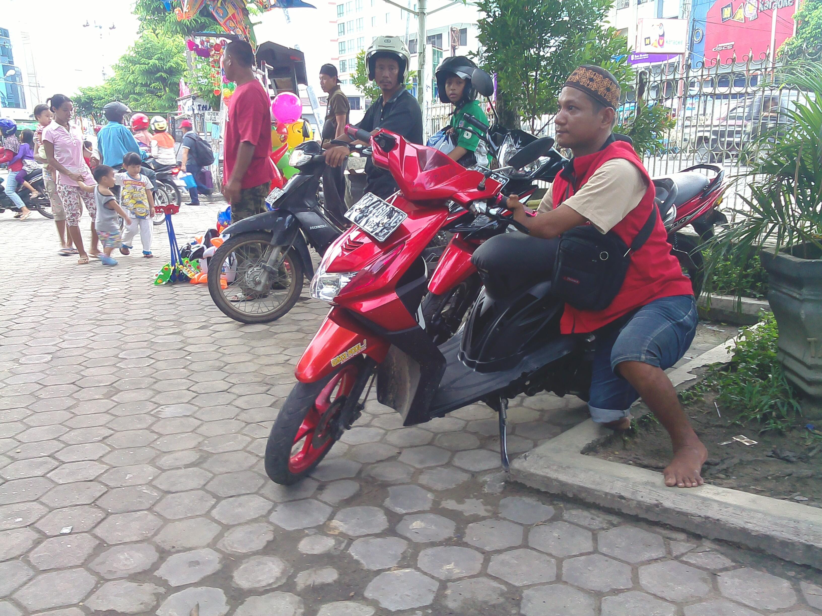Umar Sedang Mengatur Motor Yang Parkir di Pertokoan THM. (RUN)