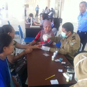 petugas kesehatan sedang memeriksa salah satu warga di bazar sembako dan pengobatan gratis bandara juata (hfa)