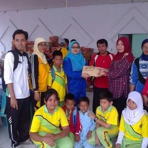 Kepala Sekolah SDN 013 Syamsiah M.Pd saat menyerahkan bantuan kepada para korban kebakaran