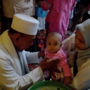 Ketua Majelis Pendidikan Al Khairat Kaltara K.H.Zainuddin Dalila Tengah Membacakan Doa  Kepada Seorang Bayi Perempuan Sebelum Dipotong Sedikit Rambutnya Dalam Rangkaian Kegiatan Tasmiyah Masal (run)