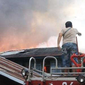 salah satu warga diatas mobil pmk berusaha padamkan api (hfa)