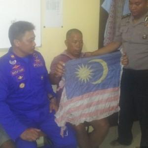 tersangka dengan membawa bendera malaysia saat diamankan petugas kepolisian (hfa)