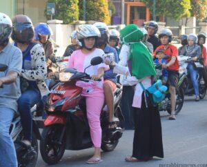 salah satu anggota KAMMI memberikan jilbab kepada pengguna jalan (hfa)