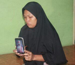 Suriani dengan menunjukan foto almarhum Sibka (hfa)