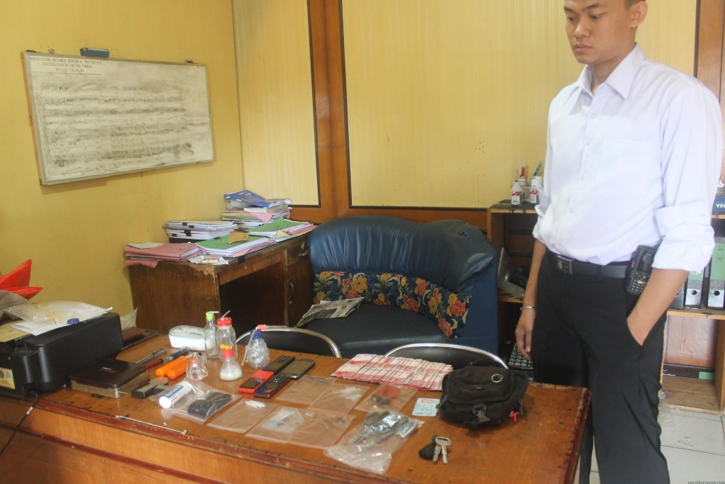 petugas polisi saat tunjukan barang bukti milik tersangka (hfa)