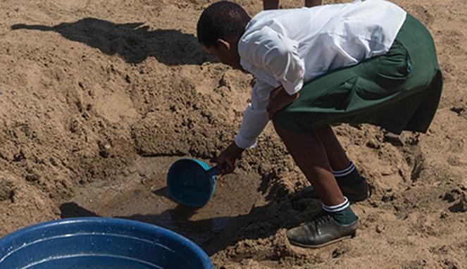seorang warga Afrika Selatan mengambil air dari oase