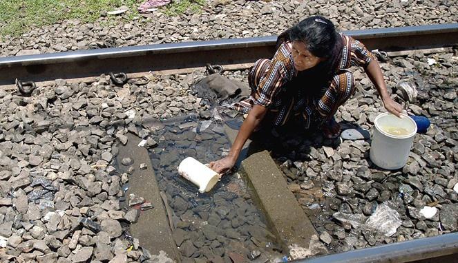 seorang wanita di India rela mengambil air dari rel kereta